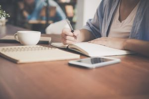 Frau sitzt am Schreibtisch und macht sich handschriftliche Notizen