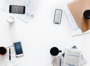 Meeting an einem Tisch mit Kaffeetassen und Handys