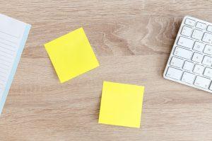 Zwei gelbe Notizzetel auf einem Holztisch mit Tastatur