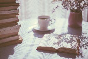Bücher auf einem Tisch mit einer Tasse Kaffee