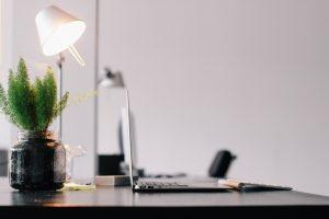 Schreibtisch mit Laptop, Lampe und Pflanze